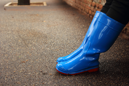 The feet in rubber boots in rainy weather. Stock Photo