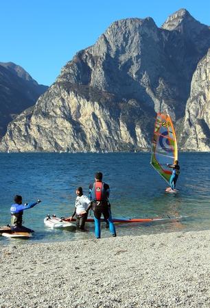 2 november: Riva del Garda, Italy, 2 November 2015, Men windsurfing, standing at the shore of the lake water.