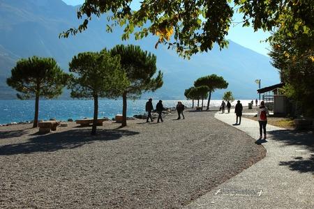 2 november: Limone sul Garda, Italy, 2 November 2015, coastline and walking tourists at Lake Garda