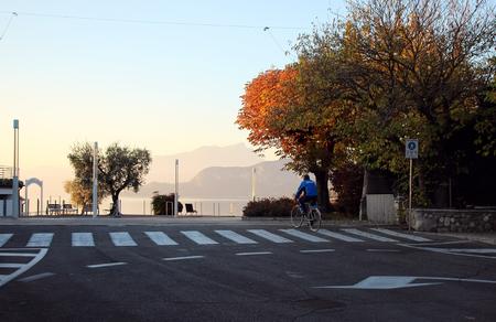 2 november: Bardolino, Italy, 2 November 2015, A man riding a bike on a deserted street.
