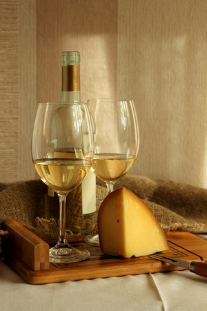 white wine: Two glasses with white wine and cheese.