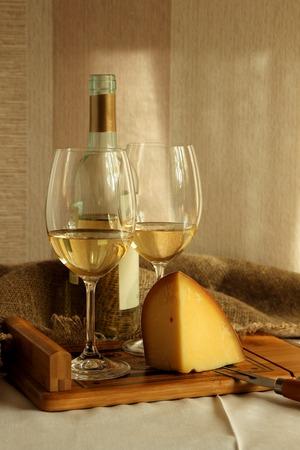 Zwei Gläser mit Weißwein und Käse. Standard-Bild