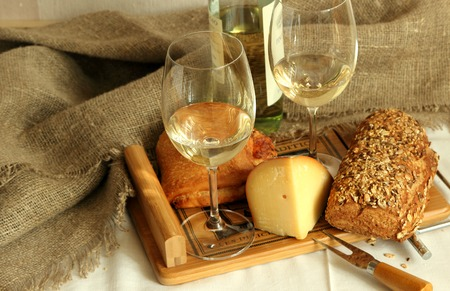 homemade bread: Two glasses with white wine, homemade bread and cheese.