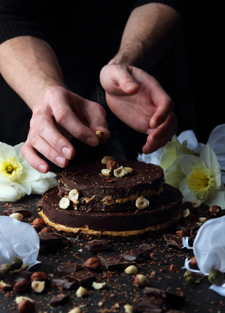 man nuts: Chocolate cake on a plate, which is decorated with hazelnuts cook. Stock Photo