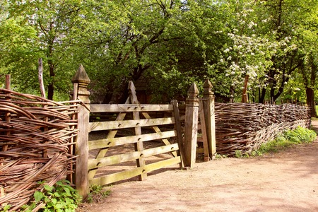 straw twig: A view of a beautiful wooden fence in a pen for animals.