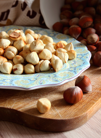 Peeled hazelnuts on a plate and nuts in the shell. Stock Photo