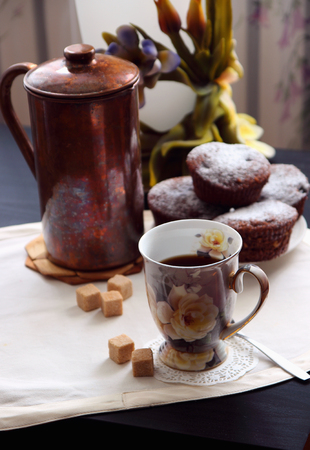 A cup of coffee and freshly baked chocolate muffins