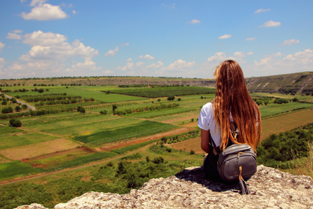 A girl sitting with her back and staring into the distance and fields.