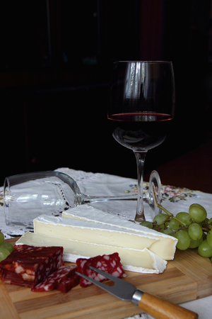 A glass of red wine, soft cheese and grapes.