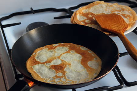 Baking the pancake in a frying pan.  Standard-Bild