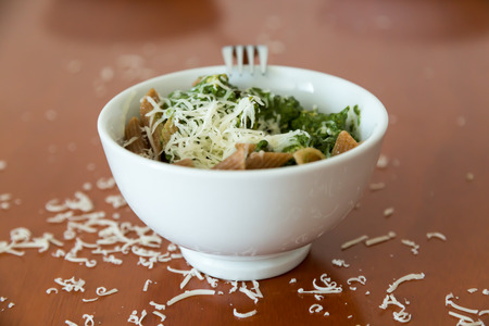 medium size: Medium size bowl filled with whole grain penne topped with cooked spinach and cheese shavings. Bowl is placed on top of brown-red table surrounded with cheese shavings. Stock Photo