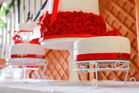Confectioner stacking a 4 tier wedding cake at the reception place and decorating it with edible red marzipan flowers