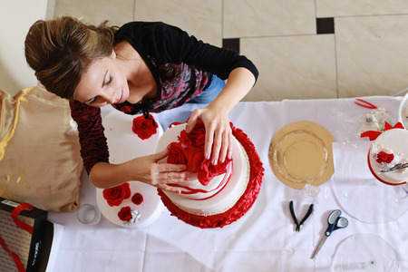 cake tier: Confectioner stacking a 4 tier wedding cake at the reception place and decorating it with edible red marzipan flowers