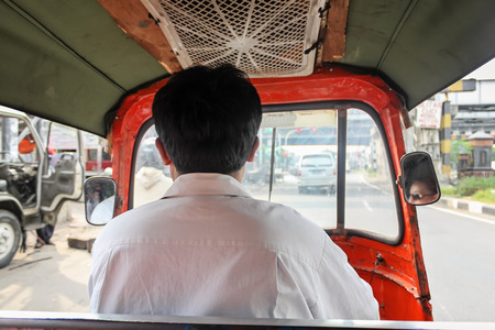 autorick: Driver driving tuk tuk - auto rickshaw , small vehicle typical for Jakarta, Indonesia