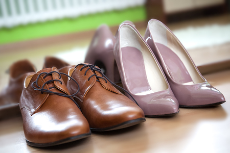 latent: Close up photo of pink latent pointy female heels and male leather camel brown lace up dress shoes, placed against mirror on the wooden floor