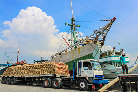 Phinisi ship with loaded truck in Sunda Kelapa Harbor, Jakarta, Indonesia. One male adult person standing on empty trailer