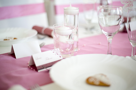 tea candle: Pink and white wedding table with small round white tea candle in a clear glass, pink runner, empty wine glasses, white plate