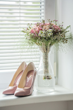 Detail of matching wedding shoes and bouquet placed in the window