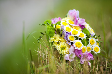 rustical: Detail of rustical small wedding bouquet made of field flowers placed on the grass in the field Stock Photo