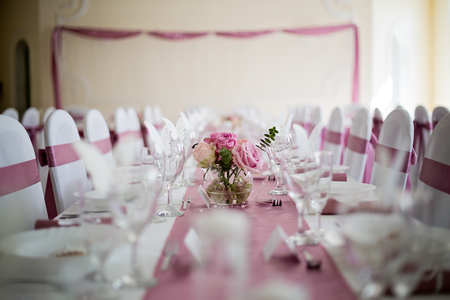 wedding table in pink and white, with roses flower center piece, empty glasses and plates, wedding reception. Stock Photo