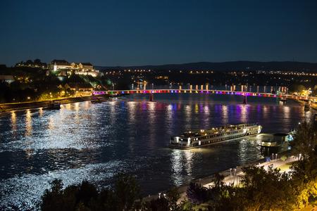 Petrovaradin fortress and Rainbow bridge over the Danube, between Novi Sad and Petrovaradin in the moonlight with ship docking