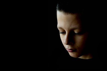 The Sad Boy With Tears in His Eye on a Black Background Foto de archivo