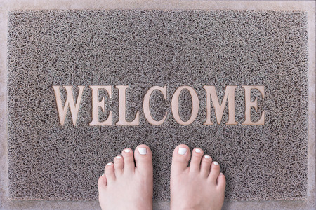 painted toenails: Welcome Door Mat With Female Feet. Friendly Grey Door Mat Closeup with Bare Woman Feet Standing. Welcome Carpet. Girl Feet with White Painted Toenails on Foot Scraper.