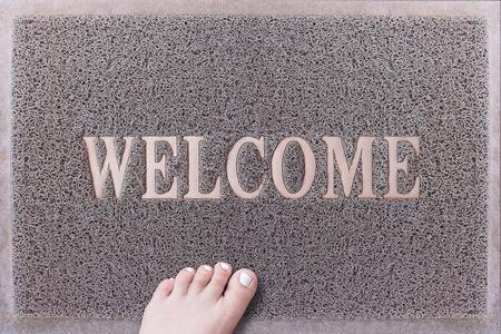u�as pintadas: Bienvenido puerta de la estera con la hembra del pie. Amistoso puerta estera gris del primer con el pie desnudo mujer de pie. Bienvenido alfombra. Ni�a de pie con blancas pintadas u�as de los pies sobre la Fiebre del raspador.