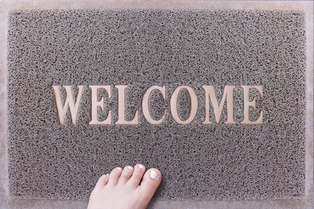 toenails: Welcome Door Mat With Female Foot. Friendly Grey Door Mat Closeup with Bare Woman Foot Standing. Welcome Carpet. Girl Foot with White Painted Toenails on Foot Scraper.