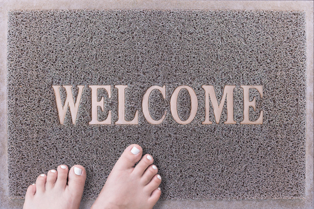 u�as pintadas: Bienvenido puerta Mat con los pies femeninos. Amistoso puerta estera gris Primer plano con los pies descalzos Mujer de pie. Bienvenido alfombra. Pies de la chica con u�as de los pies pintadas de color blanco sobre la fiebre del raspador.