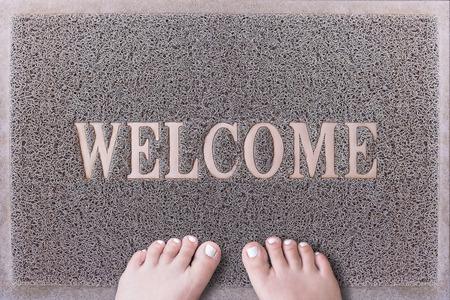 uñas pintadas: Bienvenido puerta Mat con los pies femeninos. Amistoso puerta estera gris Primer plano con los pies descalzos Mujer de pie. Bienvenido alfombra. Pies de la chica con uñas de los pies pintadas de color blanco sobre la fiebre del raspador.
