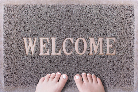 toenails: Welcome Door Mat With Female Feet. Friendly Grey Door Mat Closeup with Bare Woman Feet Standing. Welcome Carpet. Girl Feet with White Painted Toenails on Foot Scraper.