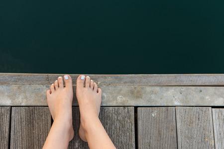 u�as pintadas: Pies femeninos en la cubierta de madera junto al mar. Los pies descalzos de la mujer con u�as de los pies pintadas de color blanco sobre fondo de madera. Foto de archivo