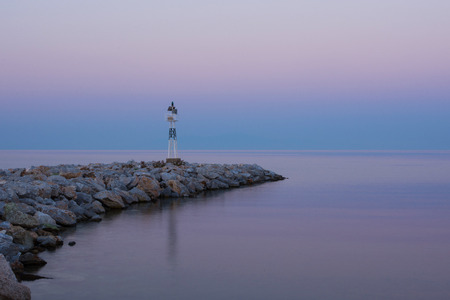 Lighthouse at Sunrise on the Rocky Coast. Dawning and Calm Sea in the Background. Reklamní fotografie