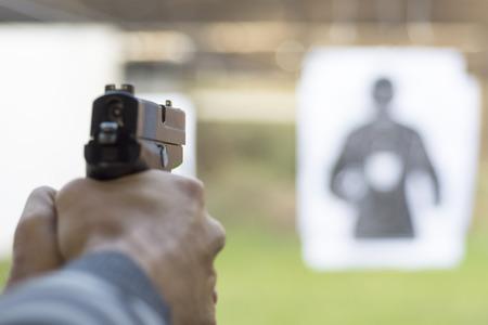 Man Firing Pistol at Target in Shooting Range