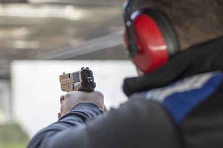 銃と射撃のターゲットでの撮影。男は火のピストル射撃の練習します。