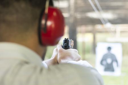 Shooting with Gun at Target in Shooting Range. Man Practicing Fire Pistol Shooting. Reklamní fotografie