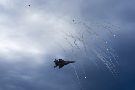 exploding: Air Strike. Fighter Jet in Dogfight. Aircraft in Battle Firing Defense Flares. War Zone. Stock Photo