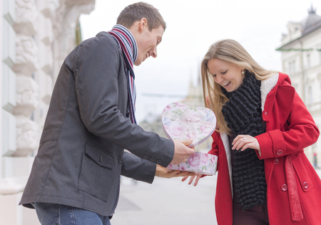 fun day: Handsome Young Man Giving His Girlfriend a Gift Box While Standing on the Street. Love and Valentines Day Concept.
