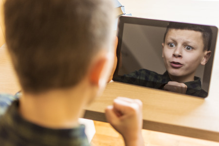 expressive face: Happy Boy Playing Tablet Game. Expressive Face in Reflection. Stock Photo