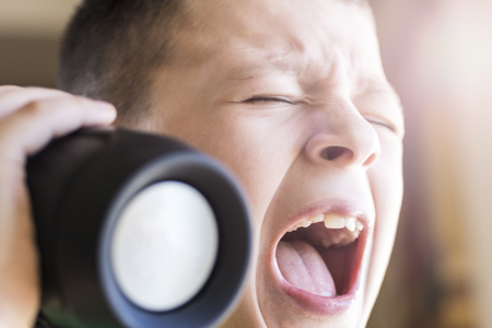expressive face: Young Boy Singing Out Loud While Listening Music on Wireless Speaker. Expressive Face. Stock Photo