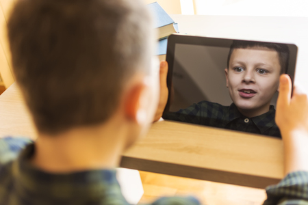 expressive face: Boy Playing Tablet Game. Expressive Face in Reflection.