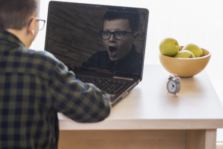expressive face: Shocked Boy With Glasses Using Laptop Computer While Sitting on Desk at Home. Expressive Face in Reflection. Stock Photo