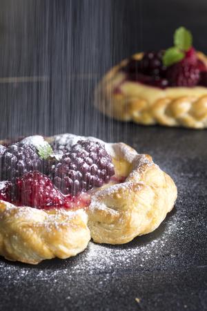 Vanilla Cream and Fruit Berry Puff Pastry Dessert Sprinkled with Powdered Sugar on Dark Background
