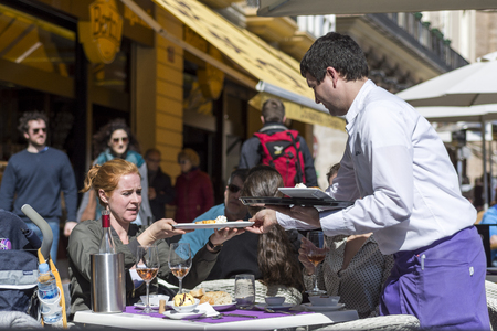 hotel staff: Waiter Serving a Lunch Plate to a Woman Guest in a Outside Restaurant