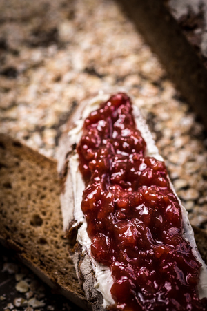 whole wheat toast: Fruity Jam on Traditional Whole Grain Rye Bread on Dark Wooden Table Background Stock Photo