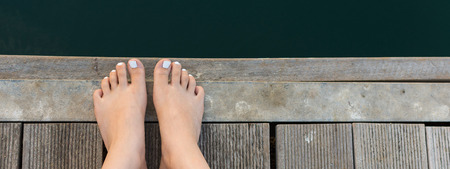 painted toenails: Female Feet on Wooden Deck by the Sea. Bare Woman Feet with White Painted Toenails on Wooden Background.