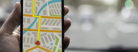 Navigazione GPS sul dispositivo mobile e il concetto di trasporto. Mano maschile utilizzando la mappa del sistema di navigazione tracciamento su smartphone con spazio di copia.