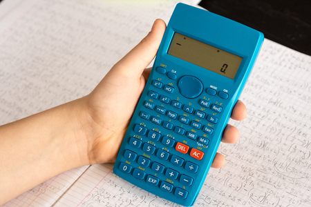 Scientific Calculator in the Action Hands During Mathematical Lesson. School Concept. 스톡 콘텐츠