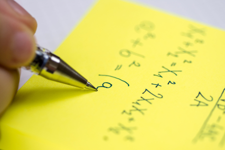 Pencil in Children Hand. Writing on Yellow Sticky Notes Close Up.